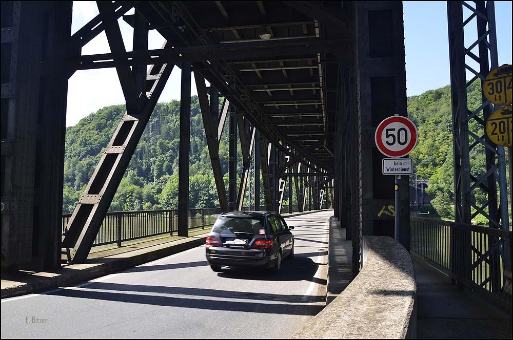 Über die Doppelstockbrücke erreicht man von Bullay aus das kleine Örtchen Alf Die Doppelstockbrücke Alf-Bullay ist die erste Doppelstockbrücke Deutschlands. Das ungewöhnliche ist, dass oben die Bahnstrecke verläuft und unten der Straßenverkehr. Nachdem die Bahnstrecke Bullay und die  Mosel passiert hat, mündet sie auf der Moselseite bei Alf direkt in den Prinzenkopftunnel, den ich gegen Ende meiner heutigen Tour noch ansehen werde. Die Brücke mit einer Länge von 314 Metern wurde 1875-1878 gebaut und zunächst als reine Eisenbahnbrücke im Zuge des Baus der Kanonenbahn geplant. Die umliegenden Gemeinden und Unternehmer beteiligten sich finanziell und so genehmigte die preußische Regierung den Bau dieser Doppelstockbrücke. Es gibt außer dieser noch zwei weitere doppelstöckige Brücken der Biggetalbahn. In Deutschland sind das die einzigen Brücken dieser Art.